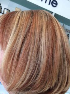 Short blonde bob with copper and red highlights