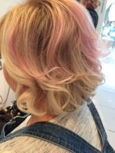 Short hair blown out with pastel pink highlights