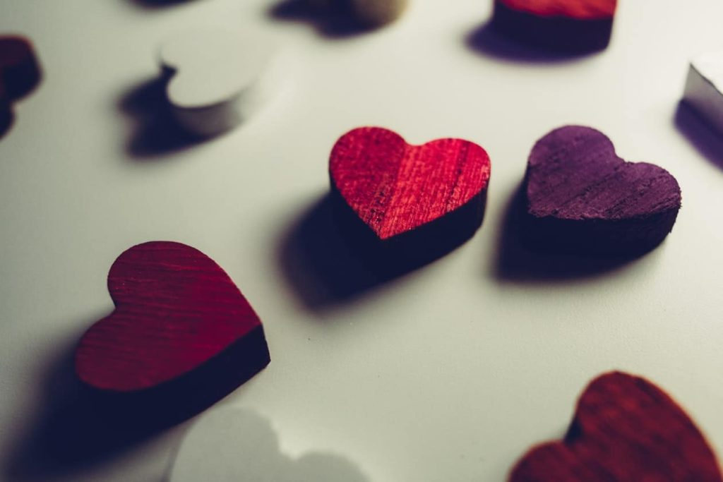 Wood carved red, purple and white hearts on white background