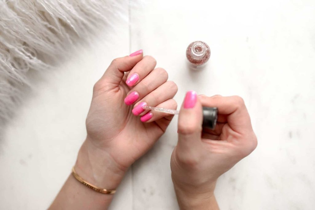 Applying glitter nail polish to nails