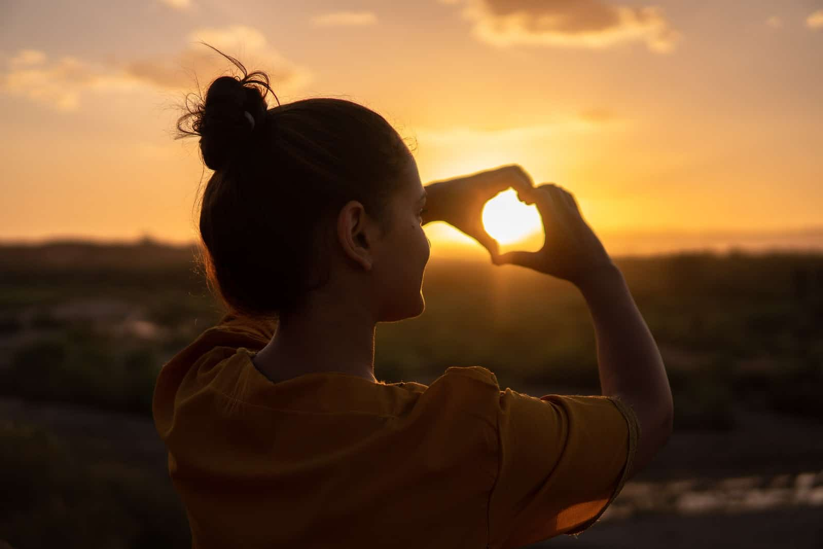 Woman making a heart symbol with hands at sunset